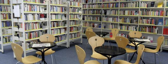 Zeigt die Fachbibliothek, den Lesebereich mit Regalen